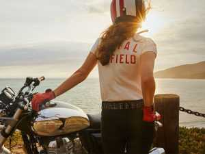 mujer motociclista con equipamiento Royal Enfield mirando el atardecer
