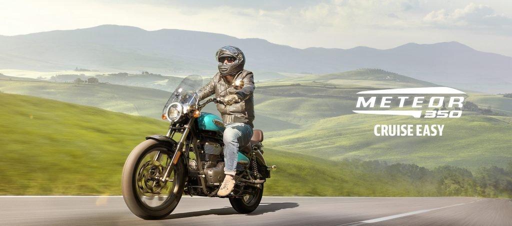 Hombre con casco y campera de cuero conduciendo una Meteor 350 en un paisaje de colinas.